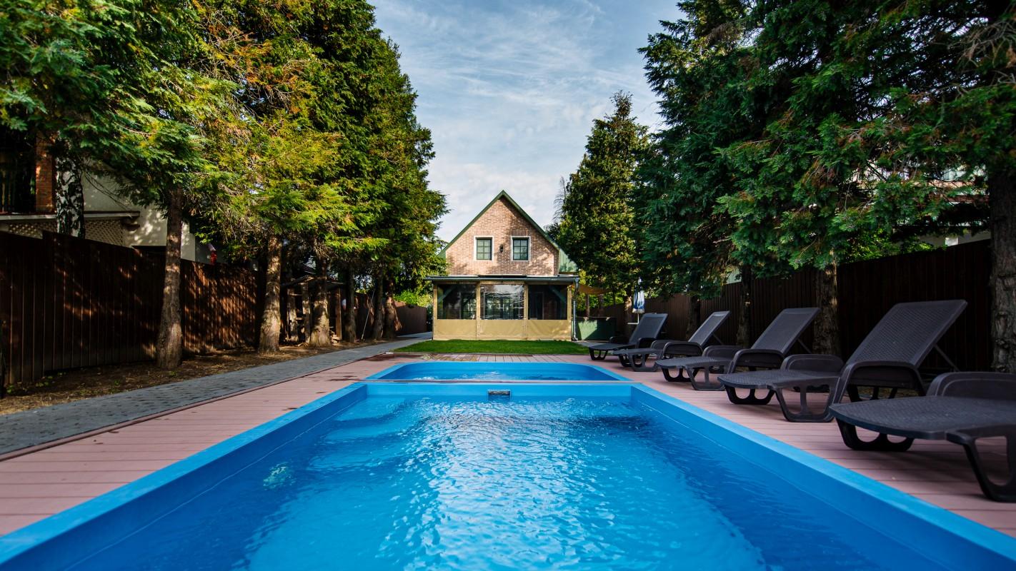 7 m x 2,5 m-es süllyesztett medence és pancsoló a kertben napozóágyakkal